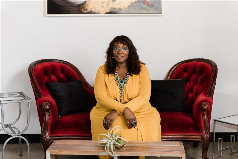 Woman in a yellow shirt and glasses sitting on a red velvet couch