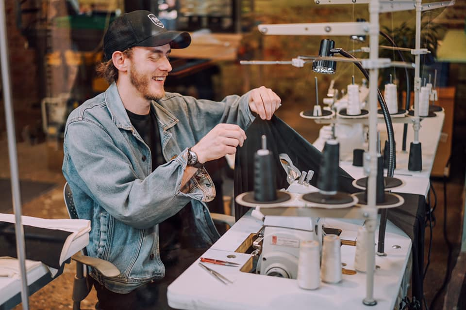 a man working with fabric in a clothing factory wearing a black hat and a jean jacket