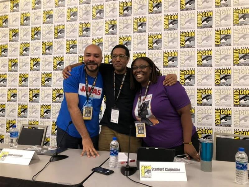 Three people embracing each other at a Comic-Con booth