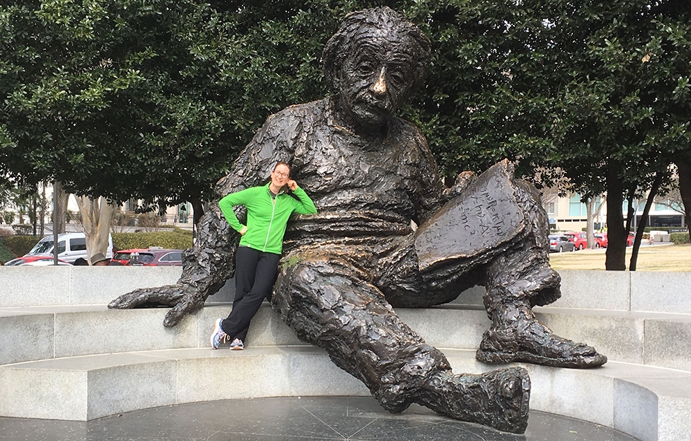 woman wearing a green jacket standing by a very large statue