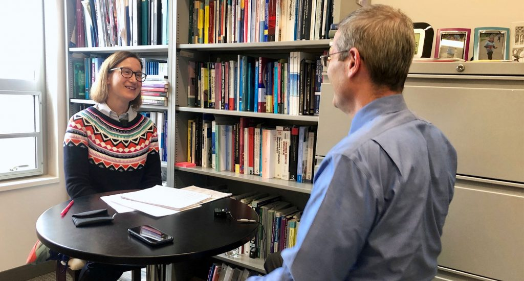 two people talking across the table in front of a book shelf